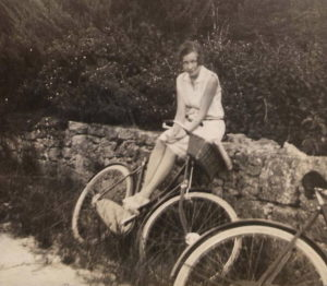 "Photo ""Bermuda, 1929. Visitor seated on stone wall with bicycles. Inherited ancestors photo "", source : Wikipedia"