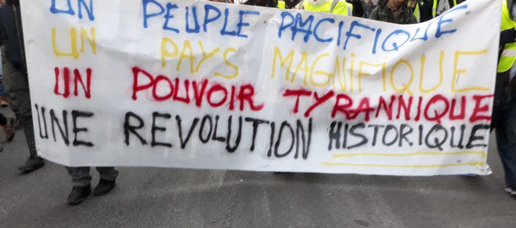 """Banderole Gilets Jaunes : """"Un peuple pacifique, un pays magnifique, un pouvoir tyrannique, une révolution historique"""""""